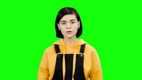 A menina em uma camiseta amarela está mostrando um dedo em um amigo Tela verde filme