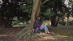 A menina em uma camiseta azul com um smartphone está sentando-se sob uma árvore com raizes de enrolamento poderosas video estoque
