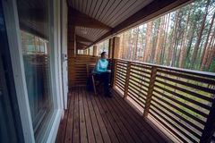 Menina em uma camiseta azul que senta-se na cadeira de madeira e no chá bebendo Imagem de Stock