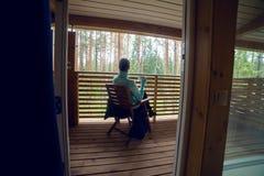 Menina em uma camiseta azul que senta-se na cadeira de madeira e no chá bebendo Imagens de Stock