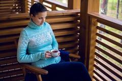 Menina em uma camiseta azul que senta-se na cadeira de madeira e no chá bebendo Imagem de Stock Royalty Free