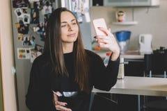 Menina em uma camiseta preta que faz o selfie e que come o cereal Fotos de Stock