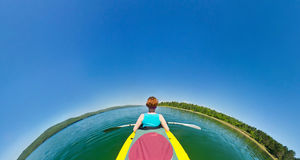 Menina em uma canoa que flutua abaixo do rio Olho de peixes Fotografia de Stock Royalty Free