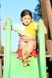 Menina em uma corrediça Fotos de Stock Royalty Free