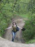 Menina em uma estrada de floresta Fotos de Stock