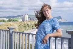 A menina em uma estreia azul da transferência das economias do vestido a menina em um vestido azul Fotos de Stock Royalty Free