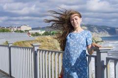 A menina em uma estreia azul da transferência das economias do vestido a menina em um vestido azul Imagens de Stock Royalty Free