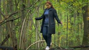 A menina em uma gola alta azul e em um cabelo vermelho nas sapatilhas brancas, vai ao longo do log de uma árvore caída video estoque
