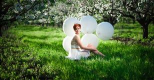 Menina em uma grama que abraça seus joelhos que olham para baixo imagem de stock