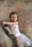 Menina em uma grande cadeira antiga Fotografia de Stock