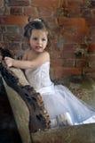 Menina em uma grande cadeira antiga Imagens de Stock Royalty Free