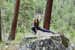 A menina em uma grande pedra que faz exercícios Imagem de Stock