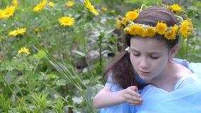 A menina em uma grinalda da mola floresce, sentando-se na grama video estoque