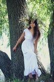 Menina em uma grinalda perto da árvore Imagens de Stock Royalty Free