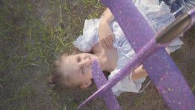 Menina em uma noite do verão durante os feriados que encontram-se sob o sol na grama e que guardam um plano do brinquedo em suas  video estoque