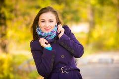 Menina em uma obscuridade - revestimento azul contra o fundo das folhas de outono Fotos de Stock Royalty Free