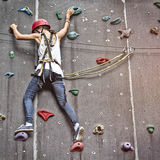 Menina em uma parede de escalada livre Fotografia de Stock