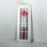 Menina em uma peruca vermelha e em uma porta branca fotos de stock royalty free