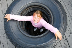 Menina em uma pilha dos pneus. Imagem de Stock Royalty Free