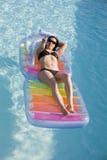 Menina em uma piscina com um inflável sunbed fotos de stock