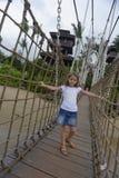 Menina em uma ponte da madeira da corda  Imagens de Stock Royalty Free