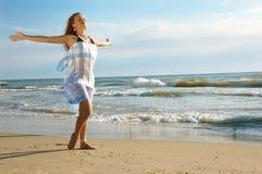 A menina em uma praia do mar está e acena a mão Imagens de Stock Royalty Free