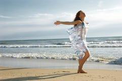 A menina em uma praia do mar está e acena a mão Imagens de Stock
