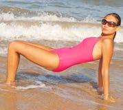 Menina em uma praia que joga no mar foto de stock