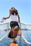 Menina em uma saia longa dos retalhos na plataforma que olha o mar Fotos de Stock