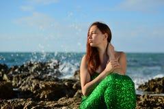 Menina em uma sereia brilhante do traje que senta-se no litoral no fundo do pulverizador e dos olhares no por do sol foto de stock royalty free