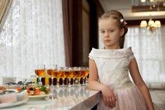 A menina em uma tabela de bufete das crianças Imagens de Stock Royalty Free