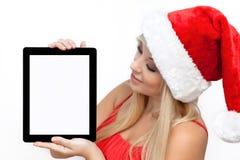 Menina em uma tabuleta vermelha da terra arrendada do chapéu do Natal Fotografia de Stock Royalty Free