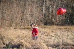 A menina em uma terra arrendada vermelha do revestimento coração-deu forma ao balão Imagens de Stock