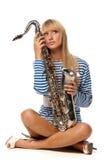 Menina em uma veste descascada com um saxofone Fotos de Stock Royalty Free