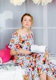 A menina em vestidos coloridos brilhantes leu o livro Flores da decoração Modo da mola Fotografia de Stock