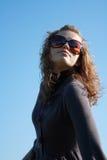 A menina em vidros de sol levanta de encontro ao céu azul Imagens de Stock