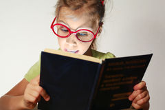 A menina em vidros vermelhos leu o livro azul Imagens de Stock Royalty Free