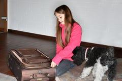 A menina embala sua mala de viagem imagem de stock royalty free