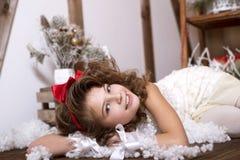 Menina emocional bonita Em um estúdio home para o ano novo e o Natal Em um vestido branco com uma curva vermelha e as peúgas Foto de Stock Royalty Free
