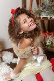 Menina emocional bonita Em um estúdio home para o ano novo e o Natal Em um vestido branco com uma curva vermelha e as peúgas Imagens de Stock