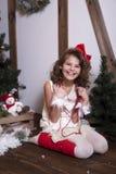 Menina emocional bonita Em um estúdio home para o ano novo e o Natal Em um vestido branco com uma curva vermelha e as peúgas Fotos de Stock