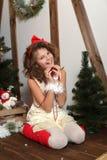 Menina emocional bonita Em um estúdio home para o ano novo e o Natal Em um vestido branco com uma curva vermelha e as peúgas Imagens de Stock Royalty Free