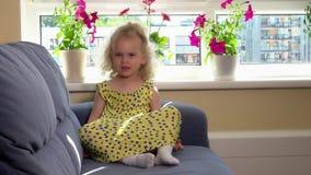 Menina emocional bonito da criança no vestido amarelo que senta-se no sofá e que mostra emoções vídeos de arquivo
