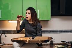 Menina emocional que come e que guarda a pizza italiana quente foto de stock royalty free