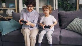 Menina emocional que joga jogos de vídeo com pouco manche da terra arrendada do filho em casa