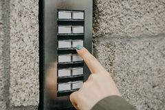 A menina empurra o botão do doorphone ou chama o intercomunicador fotos de stock