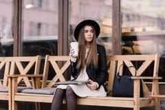 A menina encantador à moda do moderno olha pensativamente de lado ao descansar após o trabalho no laptop imagem de stock royalty free