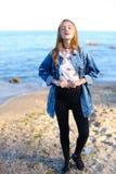 A menina encantador anda ao longo da costa e engana alegremente ao redor na areia Foto de Stock
