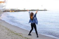 A menina encantador anda ao longo da costa e engana alegremente ao redor na areia Fotos de Stock