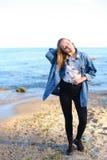 A menina encantador anda ao longo da costa e engana alegremente ao redor na areia Fotografia de Stock Royalty Free